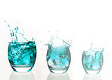 Serial arrangement of pale blue liquid splashing in tumbler