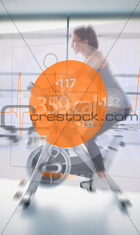 Woman riding exercise bike with futuristic interface next to her