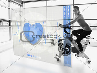 Young attractive girl doing exercise bike with futuristic interface