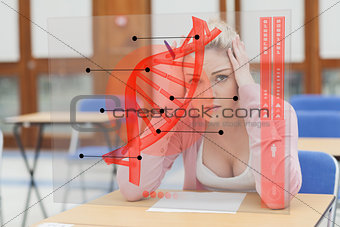 Blonde woman thinking hard while studying on futuristic interface with DNA
