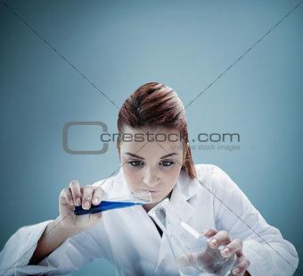 Blonde scientist pouring liquid into erlenmeyer
