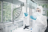 Chemist in protective suit working with futuristic interface with dna diagram