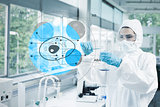 Scientist in protective suit working with cell diagram interface