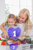 Mother and daughter chopping vegetables with purple holographic interface