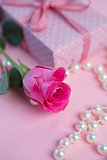 Pink rose with gift and pearls