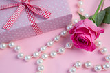 Pink rose with gift and string of pearls