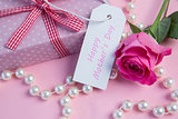 Pink rose with gift and string of pearls and tag for mothers day