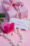 Pink rose with gift and string of pearls for mothers day