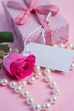 Pink rose with gift and string of pearls with blank tag