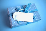 Blue gift wrapped box with blank tag