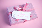 Pink gift wrapped box with happy mothers day tag