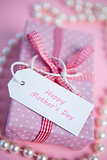 Pink gift wrapped box with mothers day greeting and pearls