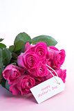 Bouquet of pink roses with happy mothers day card on a table