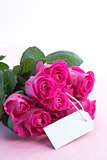 Bouquet of pink roses with an empty card on a table