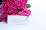 Bouquet of beautiful roses with happy mothers day card on a table