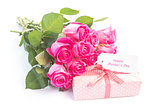 Bouquet of pink roses next to a gift with a happy birthday card