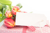 Bouquet of beautiful tulips next to a gift with an empty card