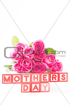 Bouquet of pink roses next to wooden blocks spelling mothers day