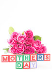 Bouquet of pink roses next to wooden blocks of different colours spelling mothers day