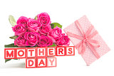 Bouquet of pink roses and pink gift next to wooden blocks spelling mothers day