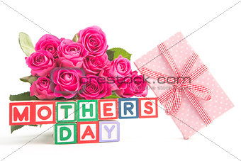 Bouquet of pink roses and pink gift next to wooden blocks of different colours spelling mothers day