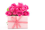 Bouquet of pink roses next to a pink gift on a white background