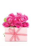 Bouquet of beautiful pink roses next to a pink gift on white background