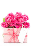 Bouquet of beautiful pink roses next to a pink gift with a blank card on white background