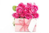 Bouquet of beautiful pink roses next to a pink gift with an empty card on white background