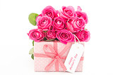 Bouquet of pink roses next to a pink gift with a happy mothers day card on white background