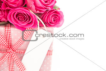 Close up of a bouquet of pink roses next to a pink gift with a blank card on a white background