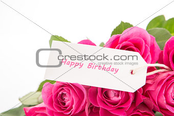 Close up of a beautiful bouquet of pink roses with a happy birthday card on a white background