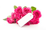 Close up of a beautiful bouquet of pink roses with an empty card on a white background