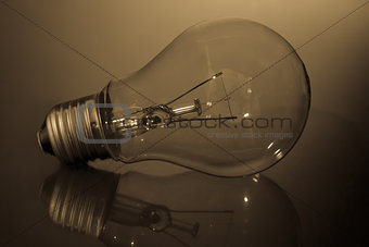 Clear light bulb laying on its side on reflective surface