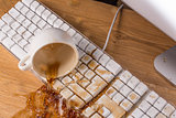 Cup of tea spilling over a keyboard