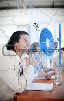 Smiling businessman looking at blue pie chart interface