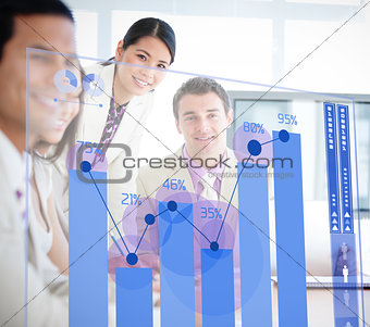 Smiling business workers looking at blue chart interface