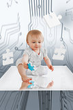 Baby holding jigsaw piece sitting on reflective surface