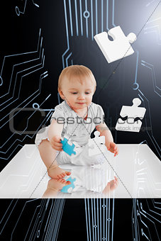 Baby holding jigsaw piece sitting on white reflective surface