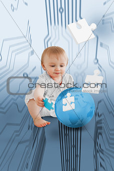 Baby holding jigsaw piece sitingt next to a globe