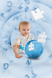 Baby holding a blue jigsaw piece sitting next to a globe