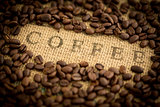 Coffee beans surrounding coffee stamped on sack