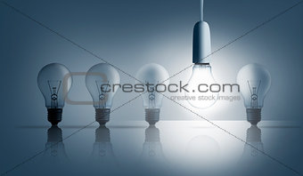 Five light bulbs in a row with one lit up