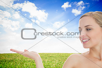 Smiling woman looking at her opened hand