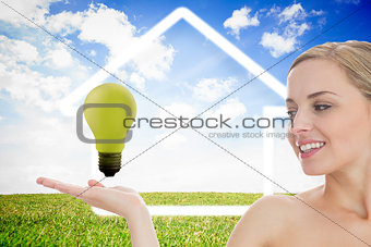 Young woman looking at green light bulb