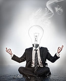 Businessman with bulb head sitting in meditation position