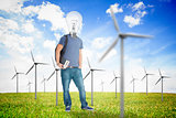 Student with a light bulb head in the middle of wind turbine field