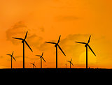 Several wind turbines with a sunset