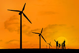Wind turbines and family jumping with a sunset