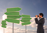 Businessman looking at empty signposts with binoculars